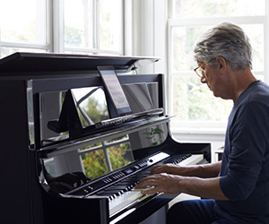 man playing digital piano with tablet